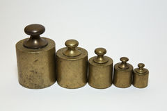 Old calibration weights in a row. Five old calibration weights in a row and  on white Royalty Free Stock Images