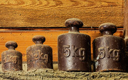 The old calibration weights in a shed at wooden wall Stock Image