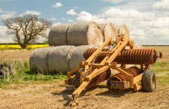Old cambridge arable roller with bales of hay. Crop field  and clouded sky Royalty Free Stock Images