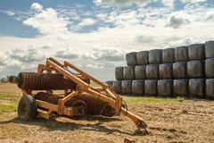 Old cambridge arable roller with bales of hay. Crop field  and clouded sky Stock Photo