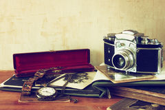Old camera, antique photographs and old pocket clock Royalty Free Stock Image