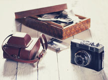 Old camera and bag , wood box with photos Royalty Free Stock Images