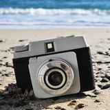 Old camera on the beach Stock Image