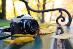 Old camera on a bench. In autumn park stock photos