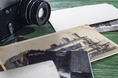 Old camera and black-and-white photos on wooden table. Royalty Free Stock Image