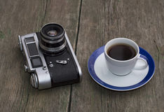 The old camera and cup of coffee on a wooden table Royalty Free Stock Photo