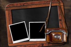 Old Camera with Empty Photos and Blackboard. Old and vintage camera with leather case, two empty instant photo frames and a blank blackboard with wooden frame Stock Photography