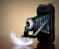 Old camera. And feather on glass table Stock Images