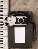 Old camera, film, piano, white flower Stock Photos