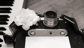 Old camera, film, piano, white flower Royalty Free Stock Photos