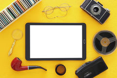 Old camera, film, tape recorder and tablet device. Top view image of old camera, film, tape recorder and tablet device over wooden yellow background. journalism Royalty Free Stock Photo
