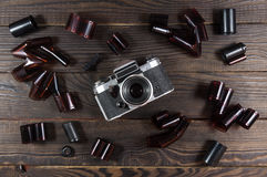 Old camera and films are on the dark wooden surface Stock Image