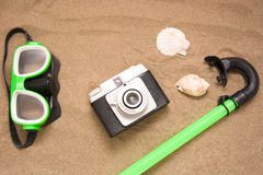 Old camera goggles  snorkel and shell tube on sand Royalty Free Stock Images