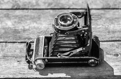Old camera in the image of an old car abstraction on a wooden background. Black and white photo of an old camera abstraction