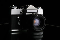 Old camera. Isolated in black Stock Photos