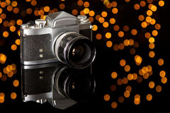 Old camera lay on reflecting surface Royalty Free Stock Images