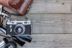 Old camera with leather case, negative films and lenses on woode. N background Royalty Free Stock Photos