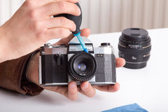 Old camera and lens in male hand Royalty Free Stock Photos