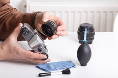 Old camera and lens in male hand. Close up of male hand removing lens from old camera for cleaning Royalty Free Stock Photography