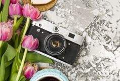 The old camera is lying on a concrete table, next to a cup with hot tea, next to it are a pink bouquet of tulip flowers. Concept breakfast, instagram, travel stock image