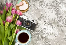 The old camera is lying on a concrete table, next to a cup with hot tea, next to a pink cookie, next to it are a pink bouquet of. Tulip flowers. Concept stock images