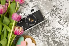 The old camera is lying on a concrete table, next to a pink cookie, next to it are a pink bouquet of tulip flowers. Concept. Breakfast, instagram, travel. There royalty free stock photography