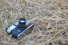 Old camera lying in the field royalty free stock images