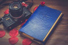 old camera and a notebook to travel and petals of flowers in decoration royalty free stock photos