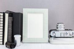 Old camera, notebooks, photo frame, roll film on grey background. Nostalgia concept design royalty free stock photo