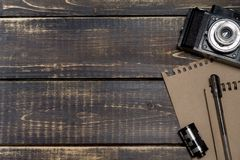 Old camera, a notepad for notes and a film on a dark wooden back. Ground, copy space Royalty Free Stock Photography