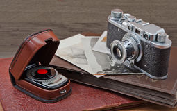 Old camera and old pictures  on wooden table, old memories. Vintage camera, photo card and photo light meter on wooden background Royalty Free Stock Photo
