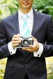 Old camera. Old photo camera in the hands of the groom Royalty Free Stock Images
