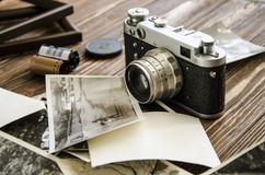 Old camera and photos on a background of brown wood Stock Photos