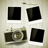 Old camera and photos lie on a wooden table. Stock  illust Royalty Free Stock Photo