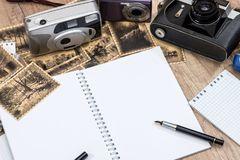 Old camera with pictures and blank notepad. On desk Stock Photography