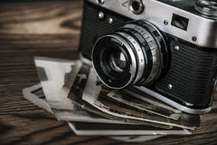 Old camera and  pictures. Old camera and old pictures wooden table Royalty Free Stock Photography