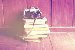 Old camera on pile of books on wooden floor royalty free stock image