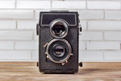 Old camera retouching Vintage on wooden table. Retro camera with two lenses royalty free stock image