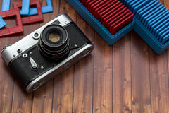 Old camera with slides. On the wooden table Royalty Free Stock Images
