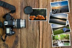Old camera and stack of photos on vintage grunge wooden background Royalty Free Stock Photos
