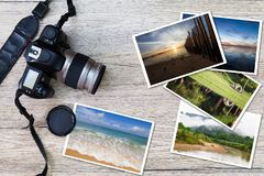 Old camera and stack of photos on vintage grunge wooden background Stock Photo