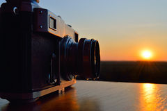 Old camera at sunset. Classic rangefinder vintage camera against a sunset sky. The picture symbolizes the sunset era of film photography Stock Photo