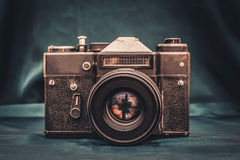 Old camera on the table. Old retro photo camera on the table on the dark green background of the fabric Royalty Free Stock Photography