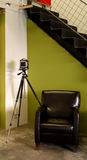 Old camera on tripod. Old camera on a tripod by a leather chair and stairs in an artist studio loft Stock Image