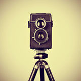 Old camera in a tripod. Picture of an old camera in a tripod with a retro effect stock photography