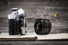 Old camera at  vintage book, wooden background. An old camera with a lens on a wooden background, space for text Stock Image