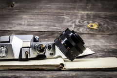 Old camera at  vintage book, wooden background. An old camera with a lens on a wooden background, space for text Stock Images