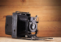 An old camera on a vintage wooden background Royalty Free Stock Image
