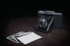 Old camera on wooden table with photographs. Picture from vintage camera on wooden table with old photographs Royalty Free Stock Image
