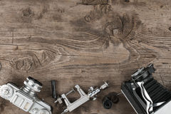 Old cameras and a tripod lie on a wooden surface. Stock Images